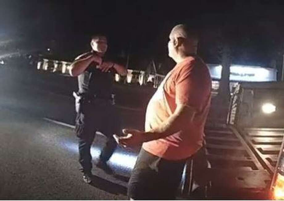 State Police Trooper Ryan Burke, left, asks Norwalk Police Officer Hector Delgado to complete a field sobriety test before charging him with DUI on Aug. 8 in Fairfield. Photo: Screenshot Of State Police Video