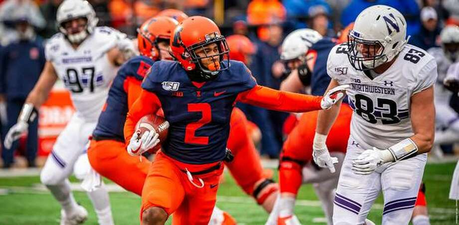 Illinois running back Reggie Corbin 92) tries to elude Northwestern's Trent Goins Saturday at Memorial Stadium in Champaign. Photo: Illinois Athletics