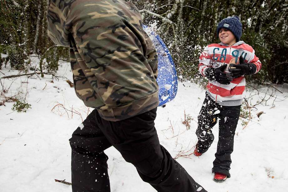 Adrian Weber (left), 16, and his brother, Brayden, 8, throw snowballs at the summit of Mount Diablo. Photo: Jessica Christian / The Chronicle