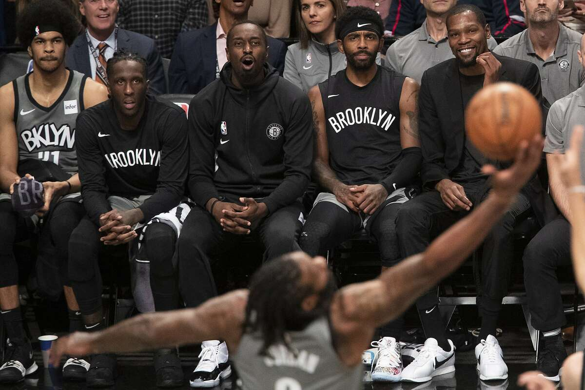 Brooklyn Nets center Jarrett Allen,forward Taurean Prince, guard Theo Pinson, guard Kyrie Irving, and forward Kevin Durant, from left, watch the game action from the bench during the second half of an NBA basketball game, Friday, Nov. 1, 2019, in New York. The Nets won 123-116. (AP Photo/Mary Altaffer)