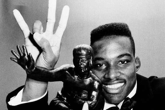 Andre Ware, posing with the Heisman Trophy in 1989, passed for 4,699 yards and 44 TDs to earn the award. He did that despite sitting the second halves of several games UH had under control.