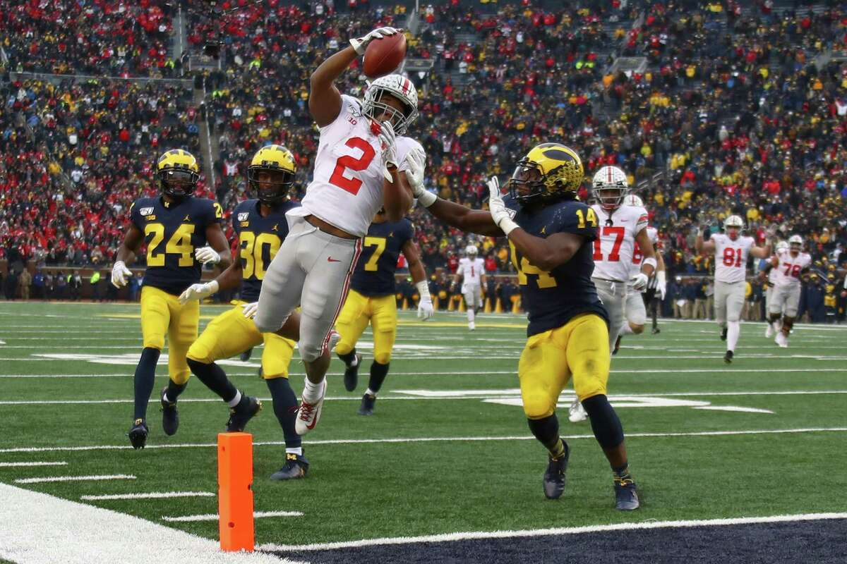 *** BESTPIX *** ANN ARBOR, MICHIGAN - NOVEMBER 30: J.K. Dobbins #2 of the Ohio State Buckeyes dives for a fourth quarter touchdown past Josh Metellus #14 of the Michigan Wolverines at Michigan Stadium on November 30, 2019 in Ann Arbor, Michigan. (Photo by Gregory Shamus/Getty Images)