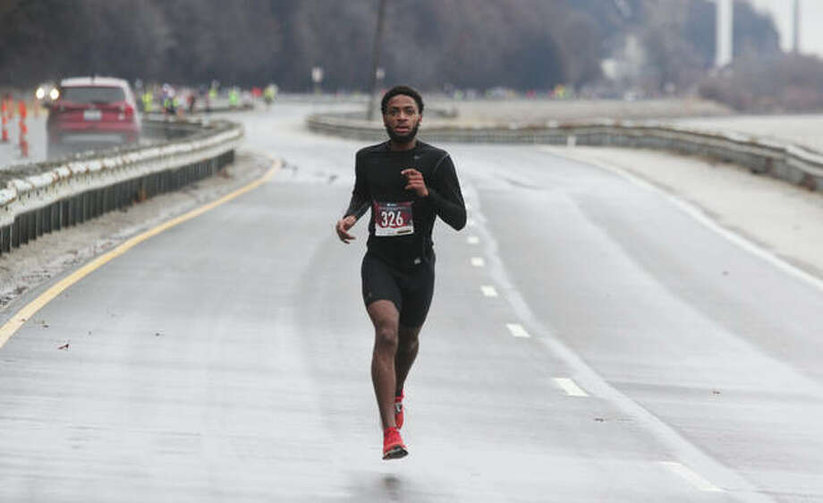 Cassius Havis, 17, of Alton, takes an early lead in the 60th annual Great River Road Run 10-mile race Saturday. He eventually finished first, with a time of 56:45.46, beating the second-place finisher by about 80 seconds. Approximately 460 people came out, despite the cold and rain, to participate in the annual event, which featured timed 10-mile and 5K runs. Photo: Scott Cousins|The Telegraph