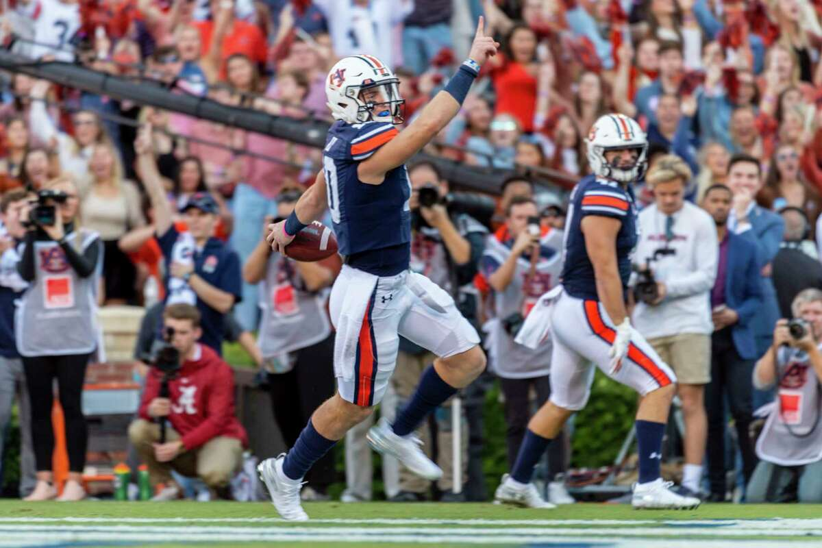 Auburn quarterback Bo Nix (10) salutes after scoring a touchdown against Alabama during the first half of an NCAA college football game, Saturday, Nov. 30, 2019, in Auburn, Ala. (AP Photo/Vasha Hunt)