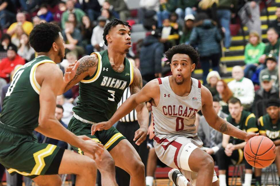 Colgate player Nelly Cummings dribbles the ball in for a layup as Siena players Manny Camper (3) and Donald Carey defend during the game on Saturday, Nov. 30, 2019 at Colgate University. Colgate won 72-62. (Alex Cooper / Utica Observer-Dispatch)
