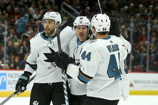 San Jose Sharks center Logan Couture (39) celebrates his goal against the Arizona Coyotes with center Barclay Goodrow, left, and defenseman Marc-Edouard Vlasic (44) during the first period of an NHL hockey game Saturday, Nov. 30, 2019, in Glendale, Ariz. (AP Photo/Ross D. Franklin)
