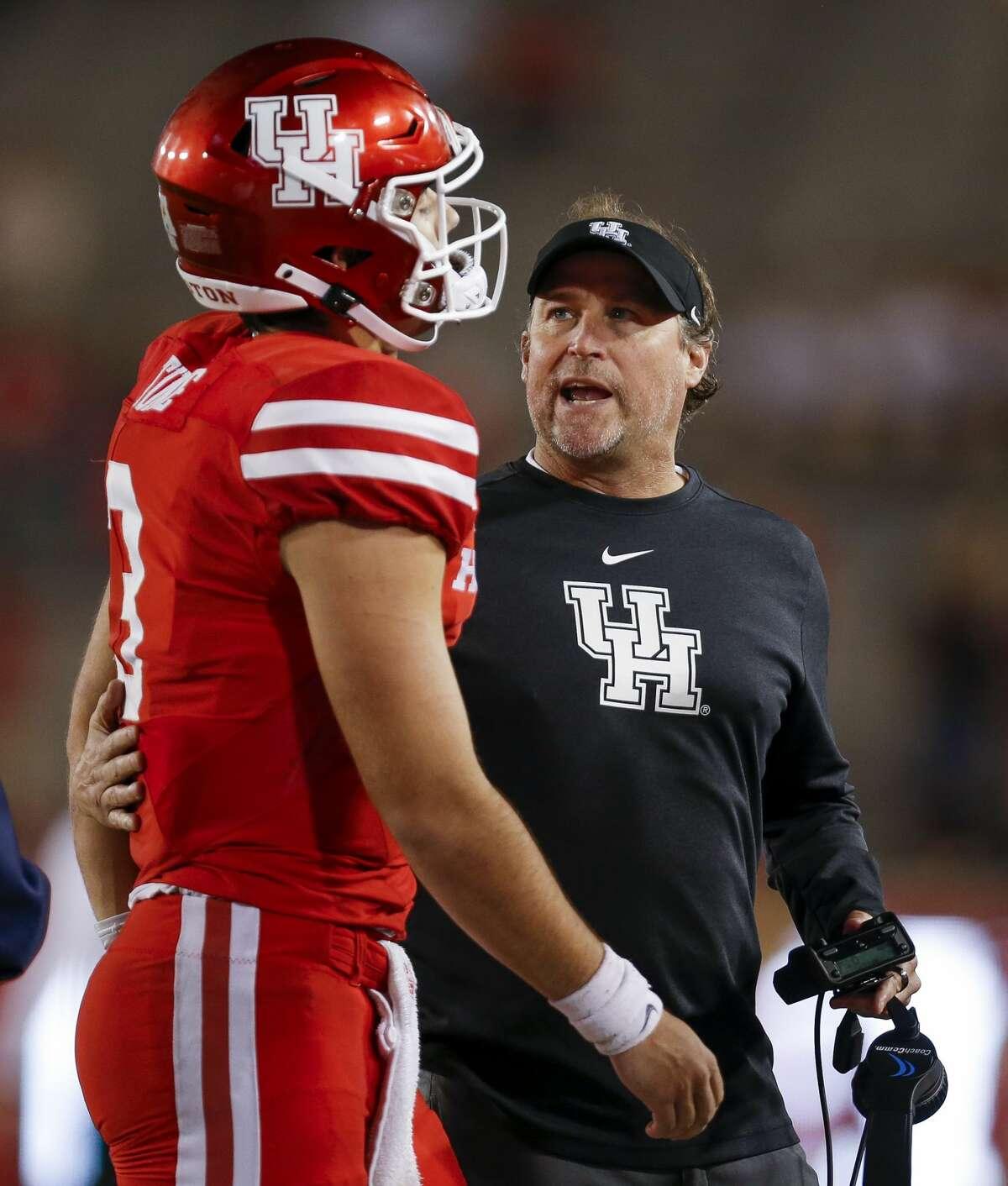 Houston Cougars head coach Dana Holgorsen talks to quarterback Clayton Tune (3) after an interception during the fourth quarter of an NCAA game against the Navy Midshipmen at TDECU Stadium Saturday, Nov. 30, 2019, in Houston. Navy won 56-41.