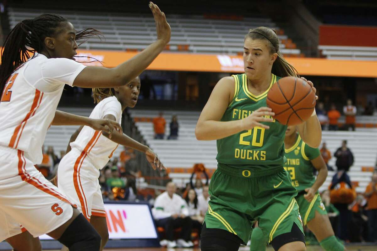 Oregon's Sabrina Ionescu, right, looks to pass the ball being guarded by Syracuse's Amaya Finklea-Guity, left, in the first quarter of an NCAA college basketball game in Syracuse, N.Y., Sunday, Nov. 24, 2019. Oregon won 81-64. (AP Photo/Nick Lisi