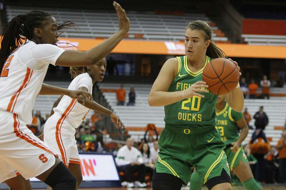 Oregon's Sabrina Ionescu, right, looks to pass the ball being guarded by Syracuse's Amaya Finklea-Guity, left, in the first quarter of an NCAA college basketball game in Syracuse, N.Y., Sunday, Nov. 24, 2019. Oregon won 81-64. (AP Photo/Nick Lisi Photo: Nick Lisi / Associated Press