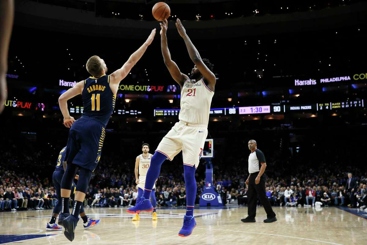 Philadelphia 76ers' Joel Embiid shoots as Indiana Pacers' Domantas Sabonis defends during the second half of an NBA basketball game Saturday, Nov. 30, 2019, in Philadelphia. (AP Photo/Matt Slocum)
