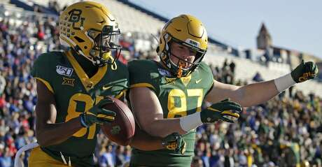 Baylor wide receiver Tyquan Thornton, left, celebrates with tight end Christoph Henle (87) after scoring a touchdown during the first half of an NCAA college football game against Kansas, Saturday, Nov. 30, 2019, in Lawrence, Kan. (AP Photo/Charlie Riedel)