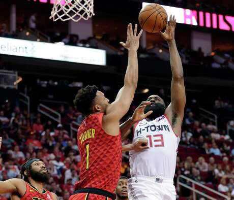 Rockets guard James Harden, right, shoots against Atlanta's Evan Turner during Saturday night's blowout of the Hawks at Toyota Center. Harden finished with his fourth career 60-point game.