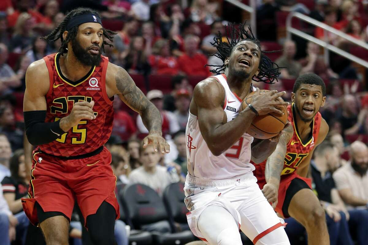 Houston Rockets guard Chris Clemons, middle, drives between Atlanta Hawks center Alex Len, left, and guard Tyrone Wallace, right, during the second half of an NBA basketball game, Saturday, Nov. 30, 2019, in Houston. (AP Photo/Michael Wyke)