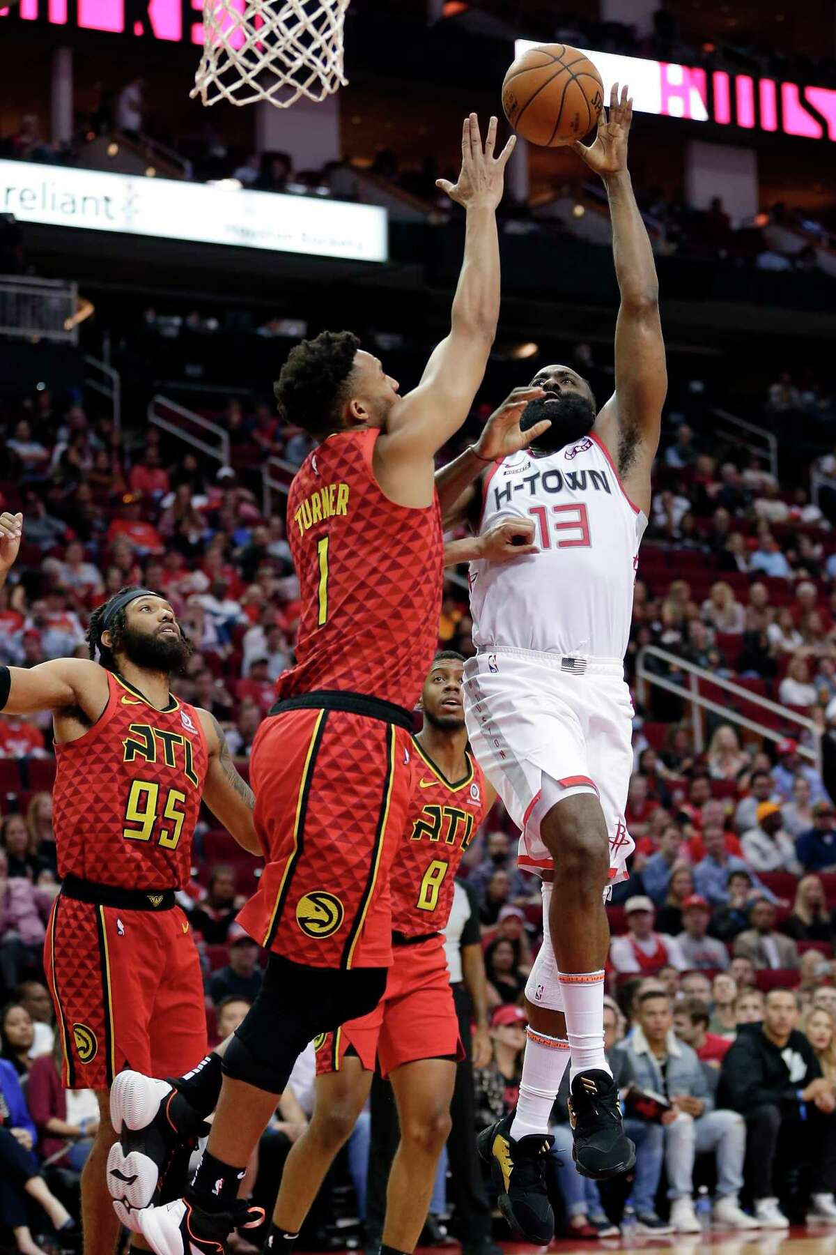 Houston Rockets guard James Harden (13) shoots against Atlanta Hawks guard Evan Turner (1) as DeAndre' Bembry (95) and Tyrone Wallace (8) look on during the second half of an NBA basketball game, Saturday, Nov. 30, 2019, in Houston. (AP Photo/Michael Wyke)