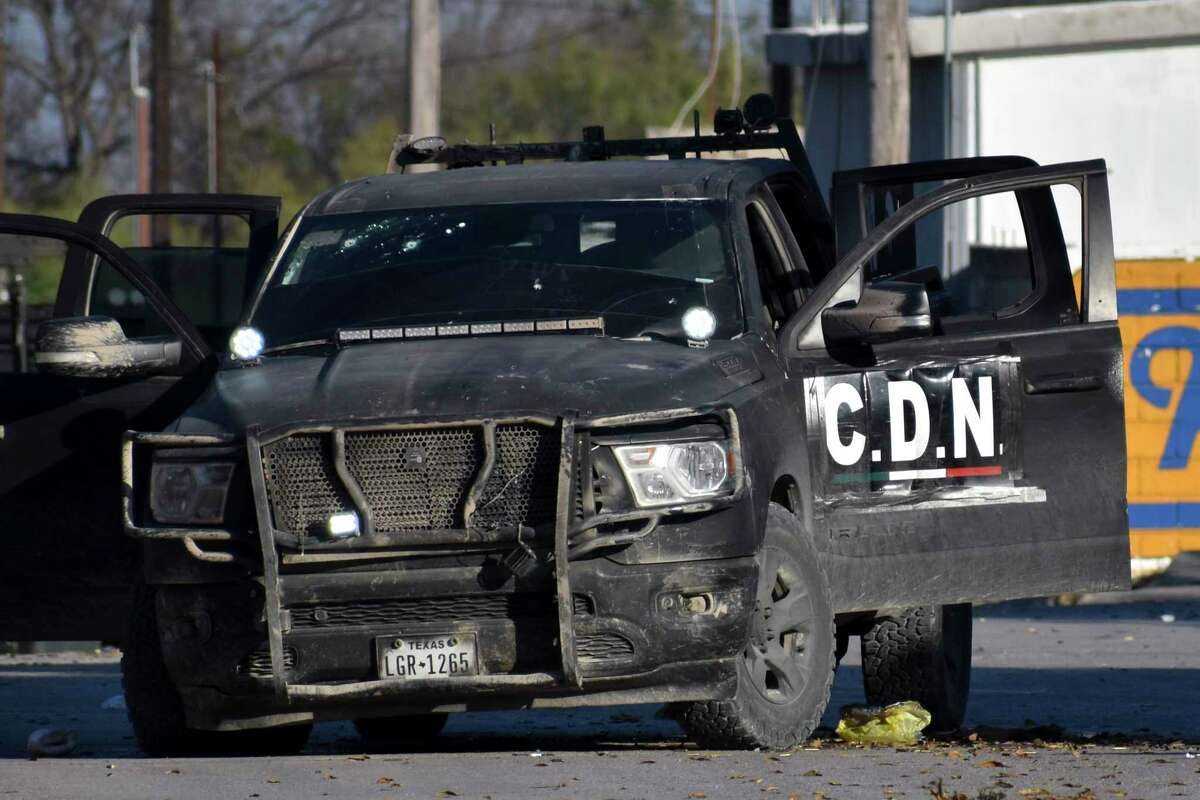 A damaged pick up marked with the initials C.D.N., that in Spanish stand for Cartel of the Northeast, is on the streets after a gun battle between Mexican security forces and suspected cartel gunmen, in Villa Union, Mexico, Saturday, Nov. 30, 2019. At least 14 people were killed, four of them police officers, after an armed group in a convoy of trucks stormed the town, in Coahuila state, prompting security forces to intervene, state Gov. Miguel Riquelme Solis said.