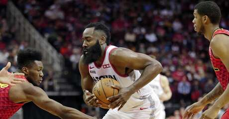 Houston Rockets guard James Harden, middle, drives between Atlanta Hawks forward Bruno Fernando, left, and guard Tyrone Wallace during the second half of an NBA basketball game, Saturday, Nov. 30, 2019, in Houston. (AP Photo/Michael Wyke)