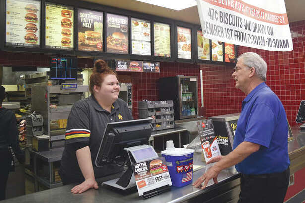 Hardee's manager Dennis Hayes (right) talks Friday to employee Desah Walden. Hayes is celebrating his 47th anniversary of working for the restaurant today.