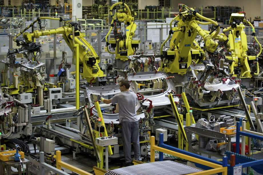 An employee positions a body panel beneath robotic arms on the production line at Hyundai Motor Co.'s plant in Nosovice, Czech Republic, on Aug. 19, 2014. Photo: Bloomberg Photo By Martin Divisek. / © 2014 Bloomberg Finance LP