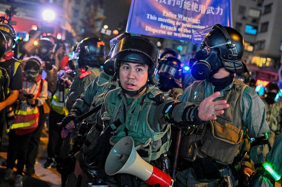 Riot officers move to disperse pro-democracy demonstrators gathered in Hong Kong. Clashes erupted Sunday, with police firing tear gas and marchers hurling bricks and smoke bombs. Photo: Philip Fong / AFP / Getty Images