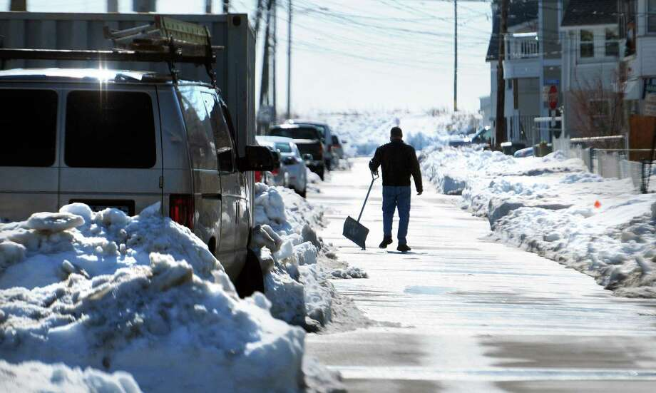 A man clears snow from around his car on East Broadway in Milford on 2/14/2013. Photo by Arnold Gold/New Haven Register AG0483B