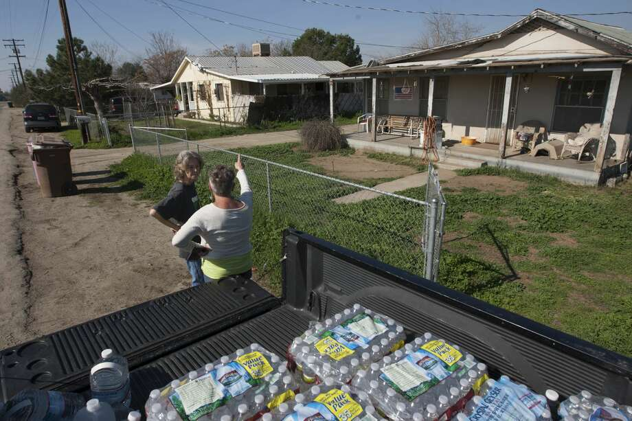 FILE: Donna Johnson and Becky Keck (L) talk as Johnson brings her water during her deliveries of donated drinking water to neighborhood households as water wells supplying hundreds of residents remain dry in the fourth year of worsening drought on February 11, 2015 in East Porterville, California. Many local residents fill water tanks with free non-potable water for flushing toilets, bathing and laundering. Bottled water is used for drinking, cooking and washing dishes. Most of the wells of about 926 dry homes in Tulare County stopped flowing last summer when some 17 California communities ran out of water. (Photo by David McNew/Getty Images) Photo: David McNew/Getty Images
