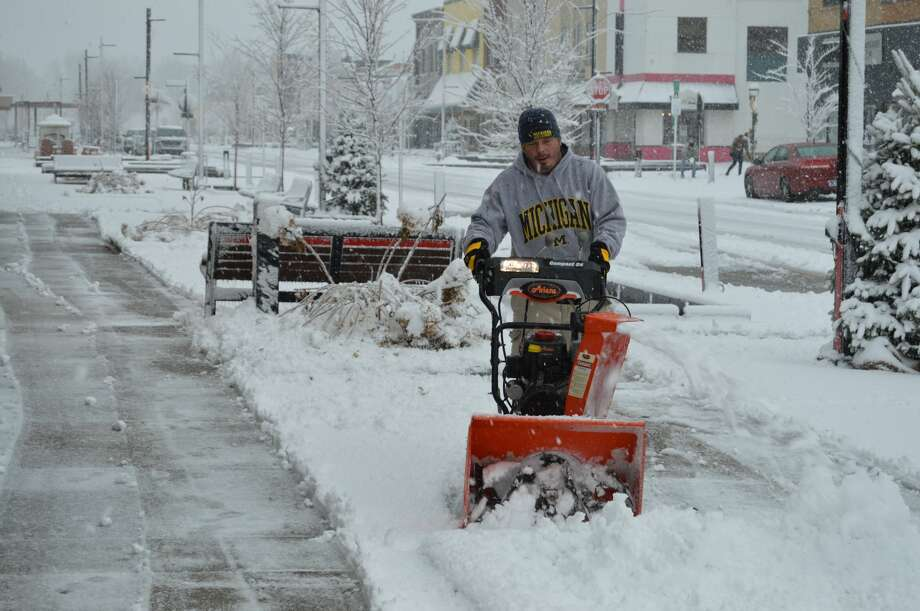 Brent Whitted, co-owner of the Grape Beginnings Winery, uses a snow-blower to clear a sidewalk in downtown Midland after an ice storm on Dec. 1. Photo: Mitchell Kukulka