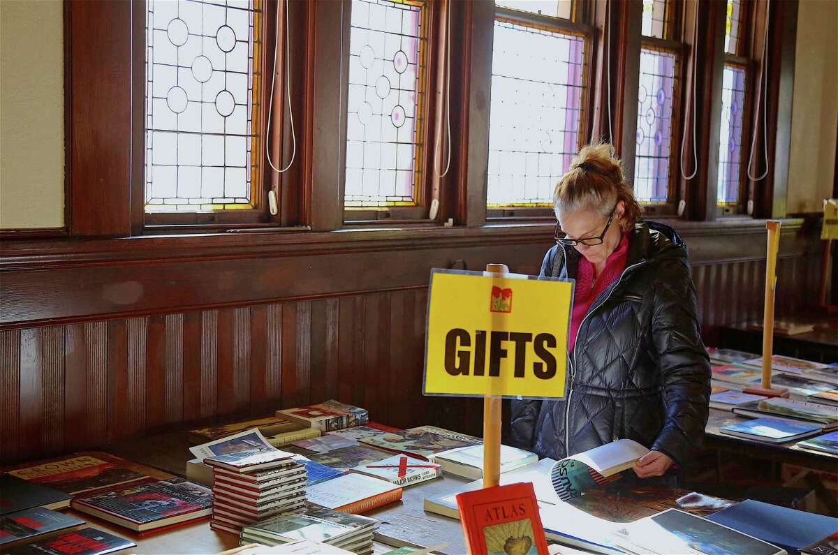 Karen Burke of Fairfield looks for some gifts at the Pequot Library's holiday book sale on Saturday, Nov. 30, 2019, in Fairfield, Conn.