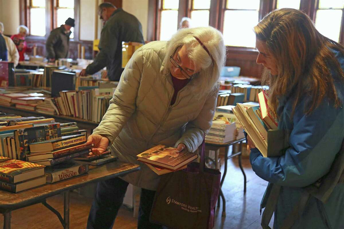 Cindy Avery of Black Rock, left, and Heather Dry of Auburn, Maine, take a closer look at the Pequot Library's holiday book sale on Saturday, Nov. 30, 2019, in Fairfield, Conn.