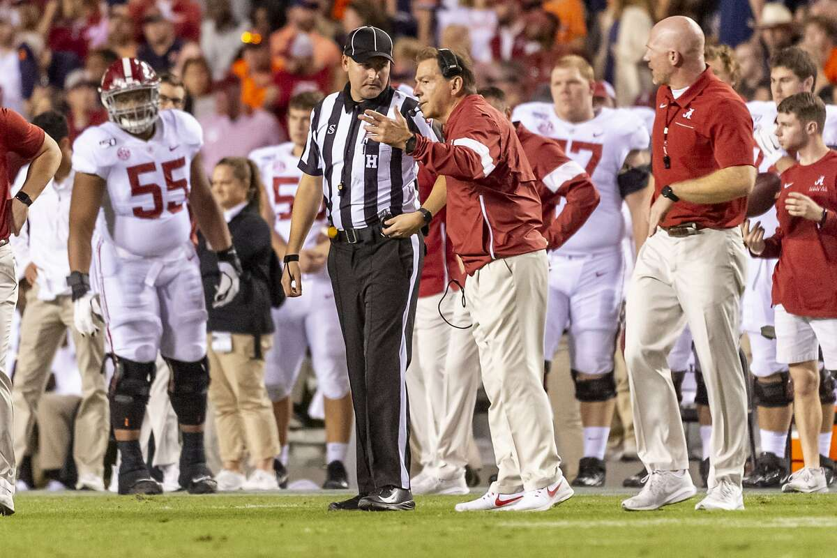 Alabama head coach Nick Saban works with a ref during the second half of Saturday's game against Auburn.