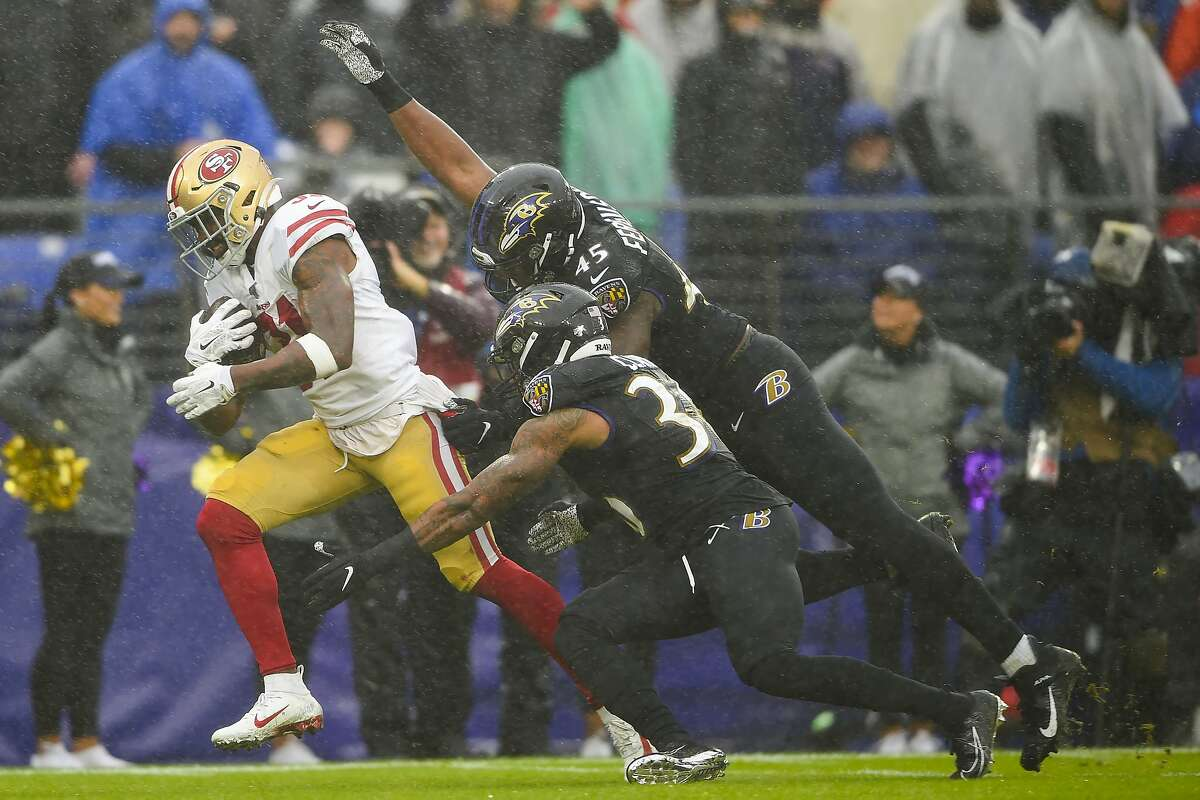 San Francisco 49ers running back Raheem Mostert (31) scores a touchdown against Baltimore Ravens defensive back Chuck Clark (36) and linebacker Jaylon Ferguson (45) in the first half of an NFL football game, Sunday, Dec. 1, 2019, in Baltimore, Md. (AP Photo/Gail Burton)