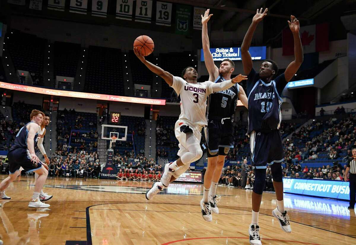 UConn's Alterique Gilbert shoots as Maine's Nedeljko Prijovic, center, and Stephane Ingo defend, right, during the first half Sunday in Hartford.