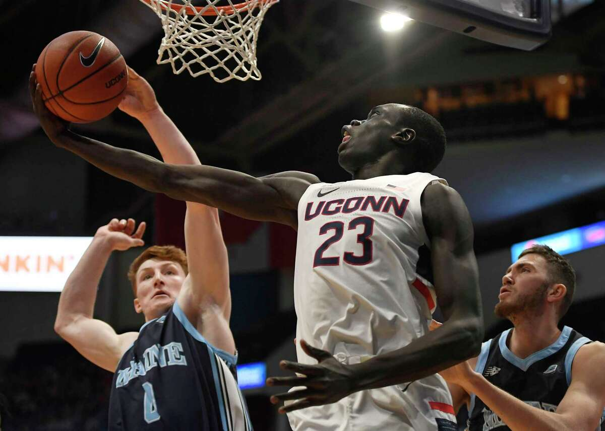 Maine's Andrew Fleming, left, blocks a shot-attempt by UConn's Akok Akok as Maine's Nedeljko Prijovic, right, defends, during the first half Sunday, Dec. 1, 2019, in Hartford.