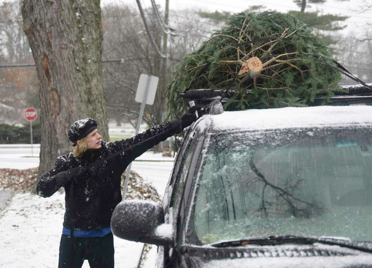 Greenwich's Ethan Singsen, 14, ties a tree to the top of his family's car at the Tree & Wreath Sale at First Congregational Church of Greenwich in Old Greenwich, Conn. Sunday, Dec. 1, 2019. FCCOG is selling top grade New Hampshire trees and wreaths with all benefits going to charities Kids in Crisis, SoundWaters, Pacific House, Building 1 Community, Mothers for Others, and The Den for Grieving Kids.