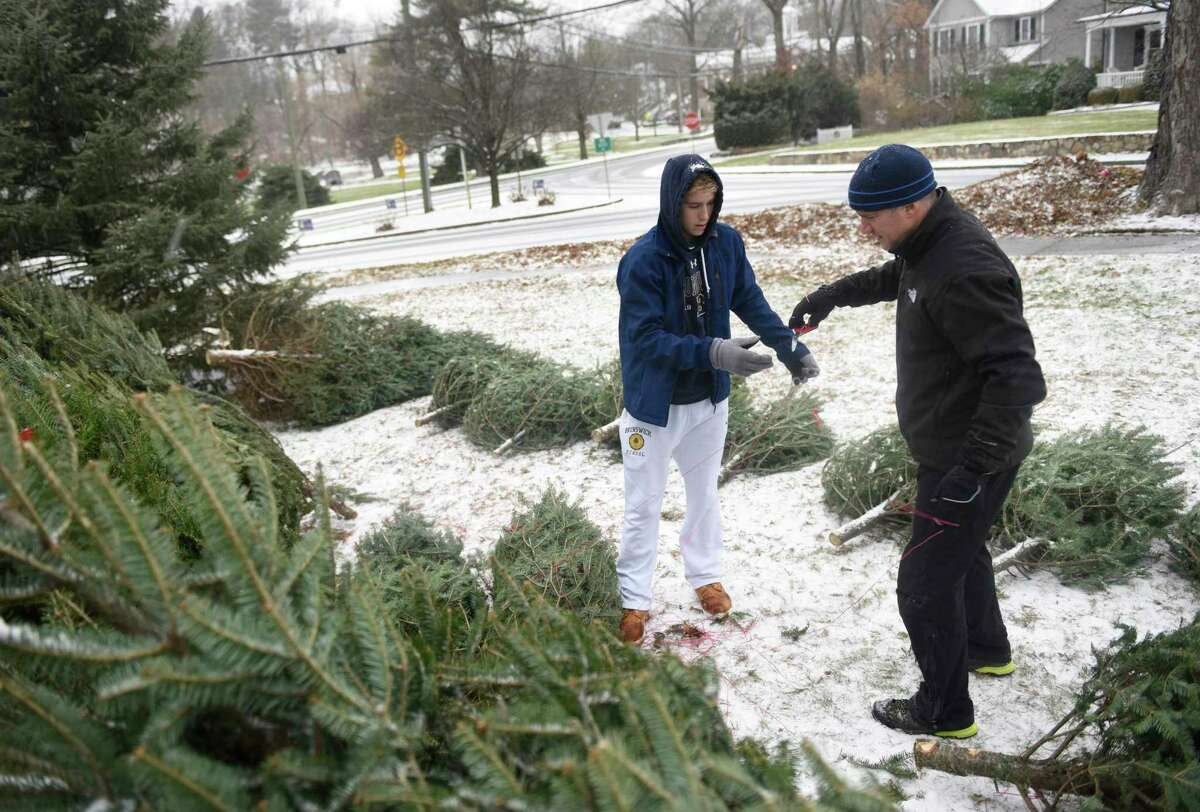 Volunteers Gavin Molly, left, 17, and Kevin Molloy sort trees at the Tree & Wreath Sale at First Congregational Church of Greenwich in Old Greenwich, Conn. Sunday, Dec. 1, 2019. FCCOG is selling top grade New Hampshire trees and wreaths with all benefits going to charities Kids in Crisis, SoundWaters, Pacific House, Building 1 Community, Mothers for Others, and The Den for Grieving Kids.