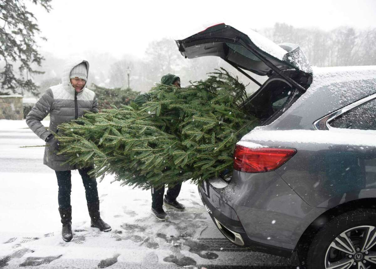 Volunteer Leslie Vandermeer helps put a tree in the trunk of a car at the Tree & Wreath Sale at First Congregational Church of Greenwich in Old Greenwich, Conn. Sunday, Dec. 1, 2019. FCCOG is selling top grade New Hampshire trees and wreaths with all benefits going to charities Kids in Crisis, SoundWaters, Pacific House, Building 1 Community, Mothers for Others, and The Den for Grieving Kids.