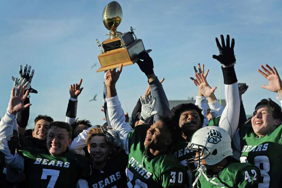 Norwalk celebrates with the Sam Testa trophy following a victory over crosstown rival McMahon in 2018. Photo: Erik Trautmann / Hearst Connecticut Media / Norwalk Hour