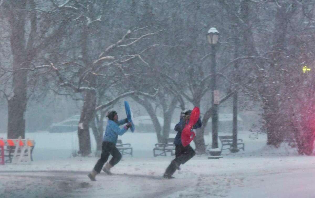 Two children with sleds run across the street near Washington Park on Sunday, Dec. 1, 2019, in Albany, N.Y. (Paul Buckowski/Times Union)