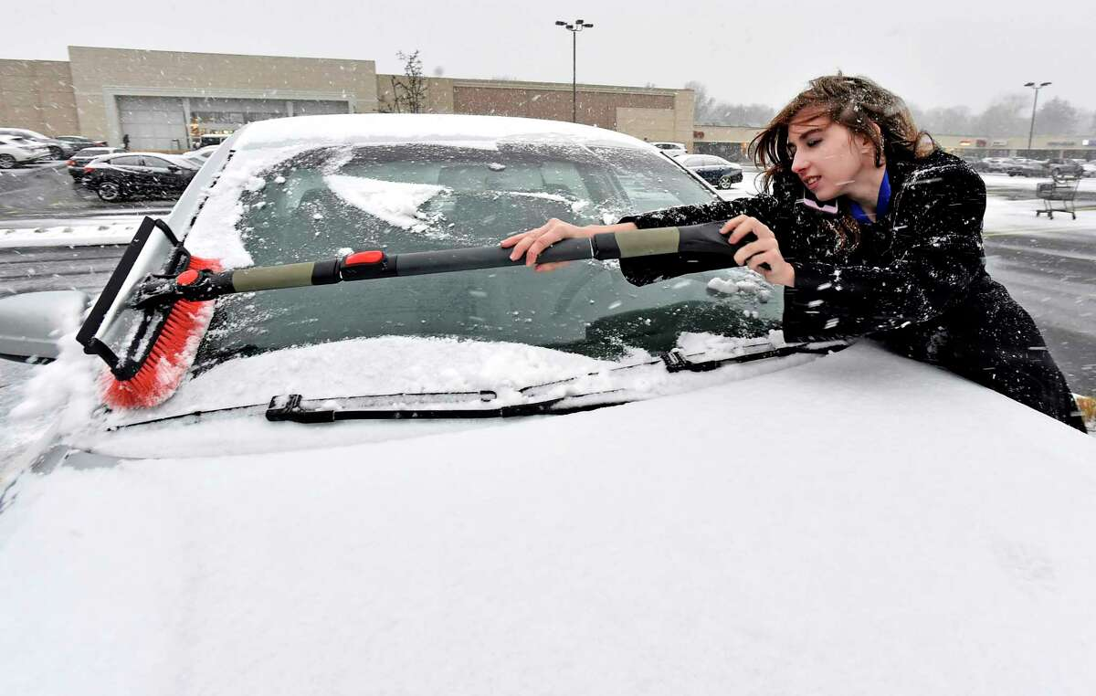 Branford, Connecticut - Sunday, December, 1, 2019: Antoinette Higgins of Branford brushes snow off her car Sunday afternoon at Branhaven Plaza in Branford as the snowstorm begins to hit New Haven County.