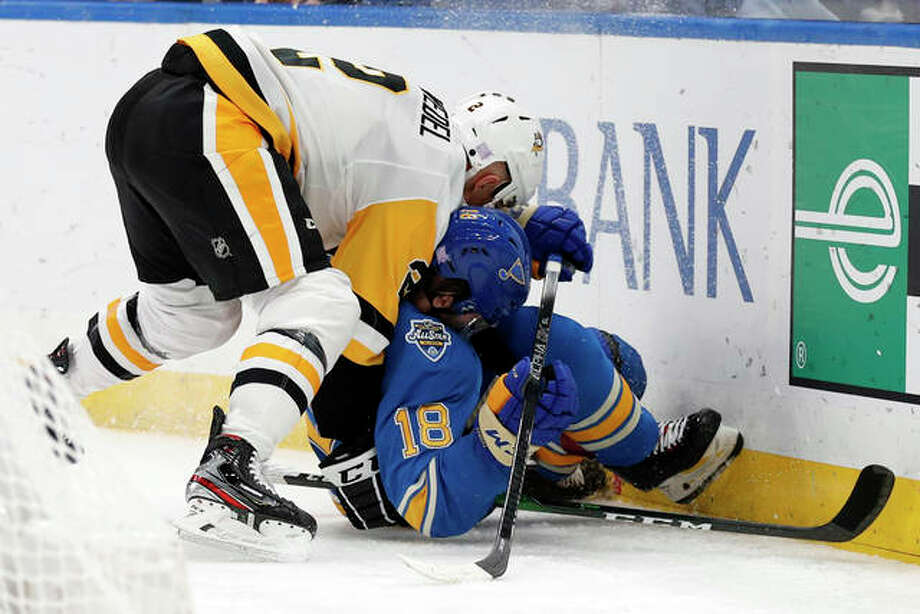 The Blues' Robert Thomas (18) and the Penguins' Chad Ruhwedel chase after a loose puck along the boards during the second period Saturday night in St. Louis. Photo: Associated Press