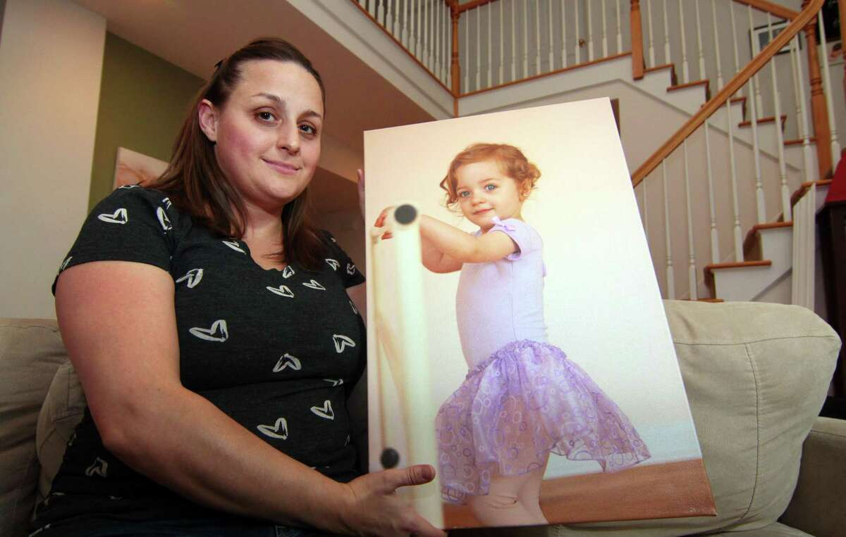 Christy Pugh poses with a photo of her daughter Emma at her home in Southbury on Tuesday. Six-year-old Emma, who attended Columbus Elementary in Norwalk died last fall of the flu. Christy is working to spread flu education and awareness.