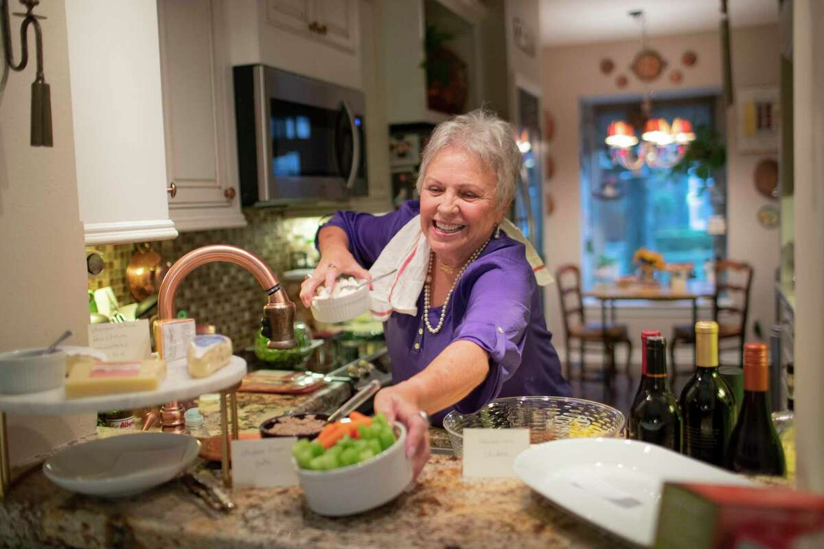 Teresa Powell, a survivor of early-stage breast and lung cancers, prepares for a cocktail party at her home on Friday, Nov. 22, 2019, in Houston. This spring, she got infusions of Keytruda, which works by unleashing a brake on the immune system to attack cancer and is approved for treatment of advanced-stage lung cancer.