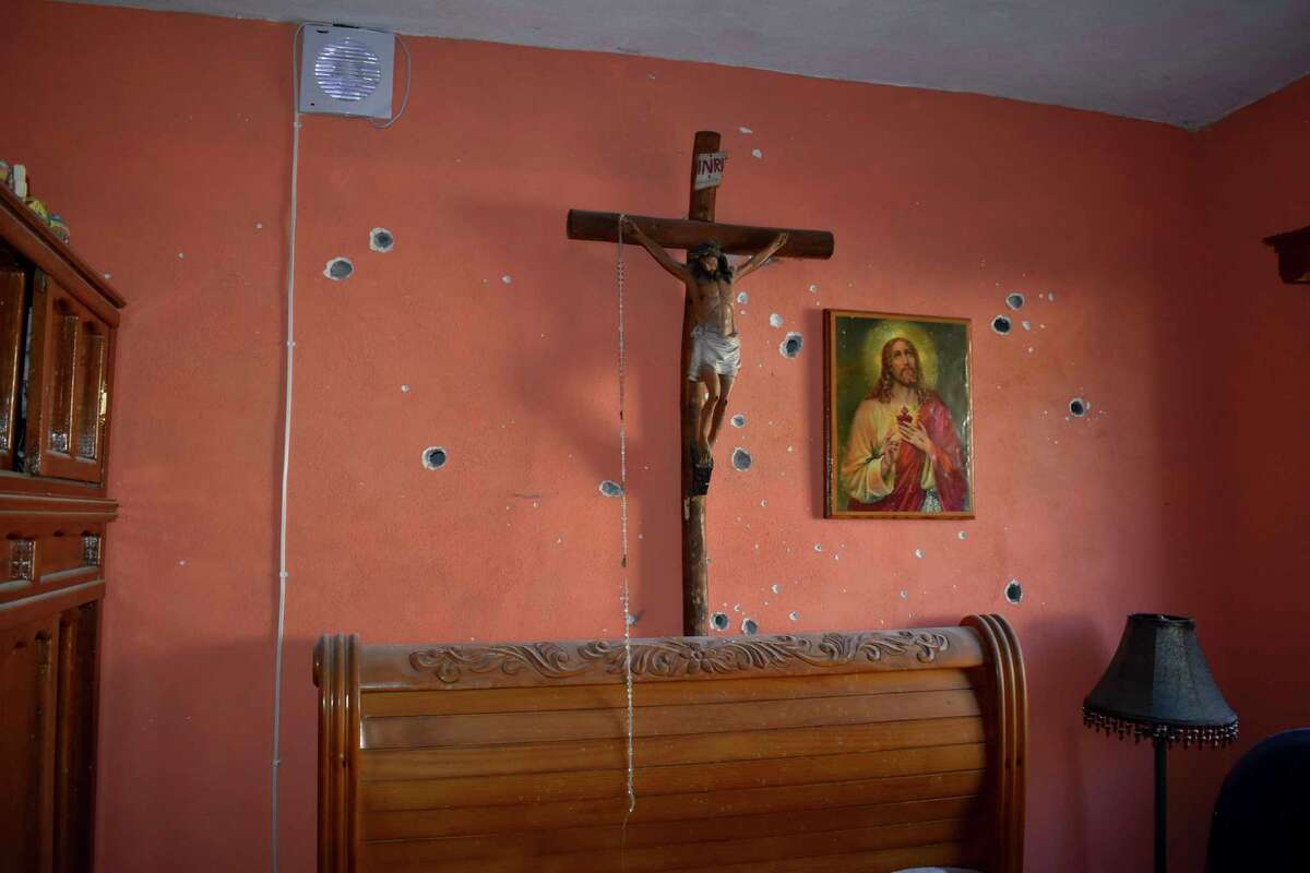 Bullet holes riddle the interior of a home after a gun battle between Mexican security forces and suspected cartel members, in Villa Union, Mexico, Saturday, Nov. 30, 2019. At least 14 people were killed, four of them police officers, after an armed group in a convoy of trucks stormed the town, in Coahuila state, prompting security forces to intervene, state Gov. Miguel Riquelme Solis said. (AP Photo/Gerardo Sanchez)