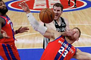 San Antonio Spurs center Jakob Poeltl fouls Detroit Pistons forward Blake Griffin (23) during the first half of an NBA basketball game, Sunday, Dec. 1, 2019, in Detroit. (AP Photo/Carlos Osorio)