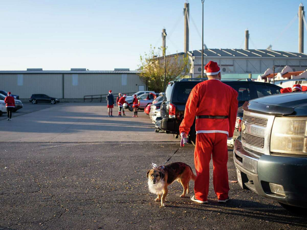 Mike Klco and his dog Addie, right, arrive in the parking lot for the 9th annual Santa Antonio 5k run in San Antonio, Texas on Sunday, December 1, 2019. Proceeds from the event go to MD Anderson to fund cancer research. Over the past 8 years the event has raised $230,000 for MD Anderson. ?'It?•s real touching to see support from the communityÉ[and from] people touched by cancer,?