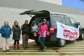 Mecosta County Sheriff's department, along with the Mecosta County Toys for Tots organization, collected donations of new, unwrapped toys for needy families for the Christmas holiday. This sheriff's cruiser was parked in front of Walmart on Perry Avenue, collecting toys for the organization. Pictured (from left) are: Janice Martin, Toys for Tots volunteer, Sheri Burch, Toys for Tots assistant coordinator, Mecosta County Sheriff's Deputy, Darcy Mann and Angela Malek, Toys for Tots Coordinator. (Pioneer photo/Cathie Crew)
