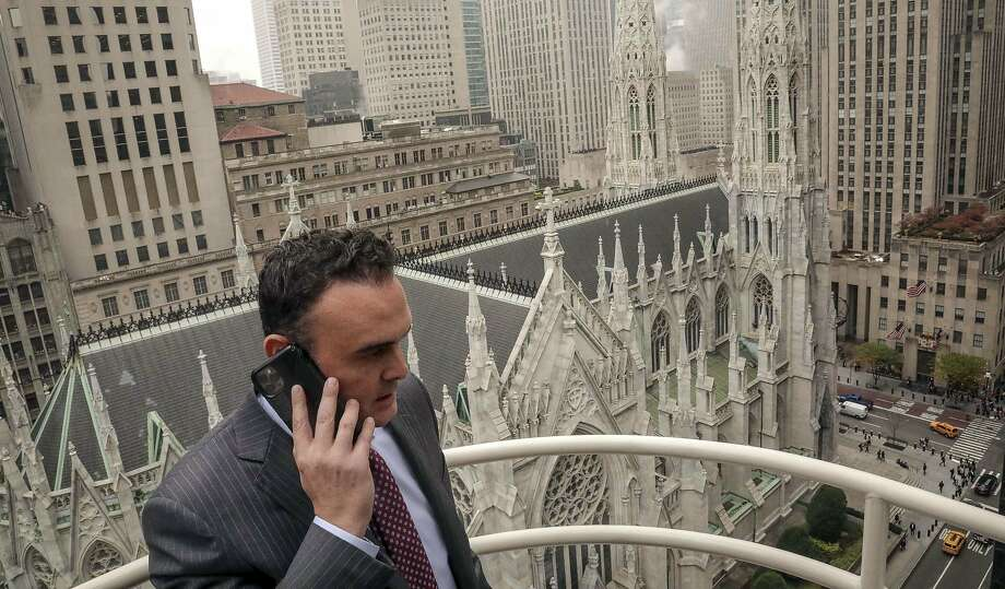 In this Tuesday, Oct. 29, 2019, photo, attorney Adam Slater takes a phone call on a patio outside his high-rise Manhattan office overlooking St. Patrick's Cathedral, in New York. Slater's firm is representing clients accusing the Roman Catholic Church of sexual abuse, a clientele that is rapidly growing after New York state opened its one-year window allowing sex abuse suits with no statute of limitations. (AP Photo/Bebeto Matthews) Photo: Bebeto Matthews, Associated Press