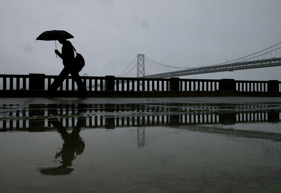 A pedestrian carries an umbrella while walking near the Bay Bridge on February 6, 2014 in San Francisco, California. The San Francisco Bay Area is getting much needed rain with up to a half inch of rain falling overnight and a bigger weather system expected to bring more precipitation over the weekend. (Photo by Justin Sullivan/Getty Images) Photo: Justin Sullivan/Getty Images