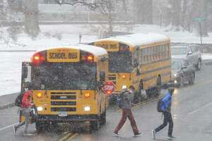 Students exit a school bus near Eastern Middle School after an early dismissal due to snow in the Riverside section of Greenwich, Conn. Tuesday, Jan. 31, 2017.
