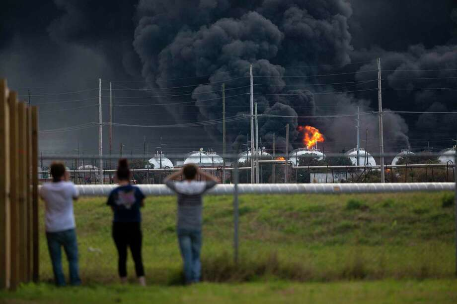 Residents observe the fire consuming the TPC Group plant on Wednesday, Nov. 27, 2019, in Port Neches, Texas.  Two massive explosions 13 hours apart tore through the chemical plant Wednesday, and one left several workers injured. (Marie D. De Jesús/Houston Chronicle via AP) Photo: Marie D. De Jesús, MBO / Associated Press / © 2019 Houston Chronicle