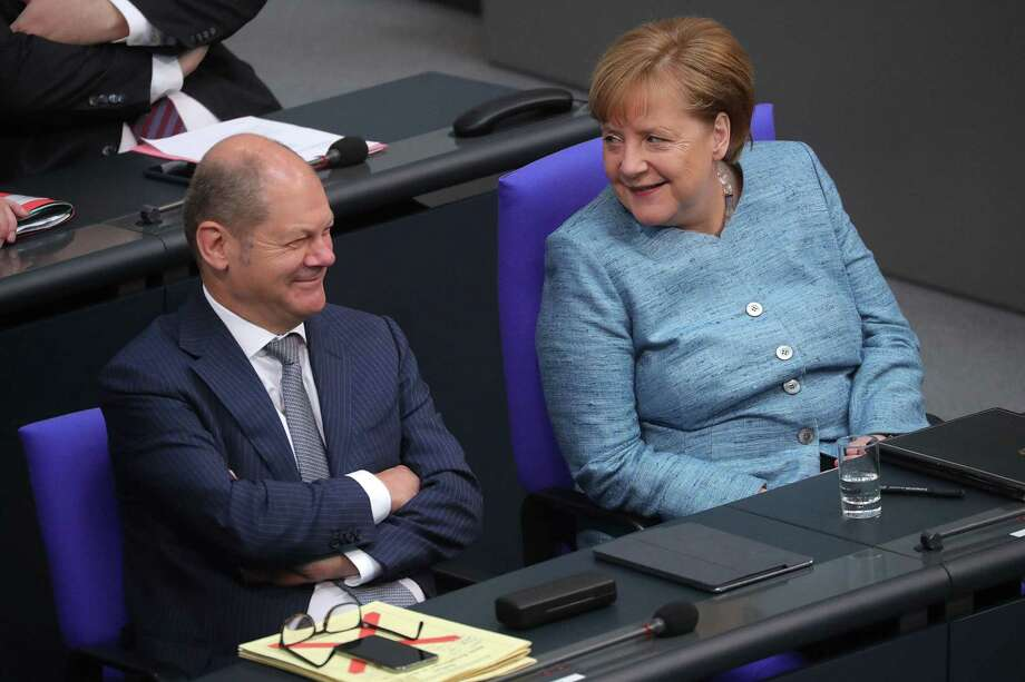 Olaf Scholz, Germany's finance minister (left) reacts as he sits beside Angela Merkel, Germany's chancellor, in the lower-house of the Bundestag in Berlin on May 16, 2018. Photo: Bloomberg Photo By Krisztian Bocsi (Bloomberg). / © 2018 Bloomberg Finance LP